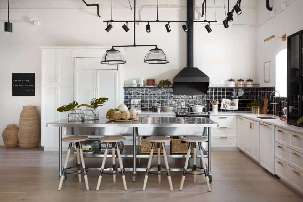 This Fixer Upper Kitchen is a mix of modern and industiral. It has a share black and white color scheme with metal and wood accents.