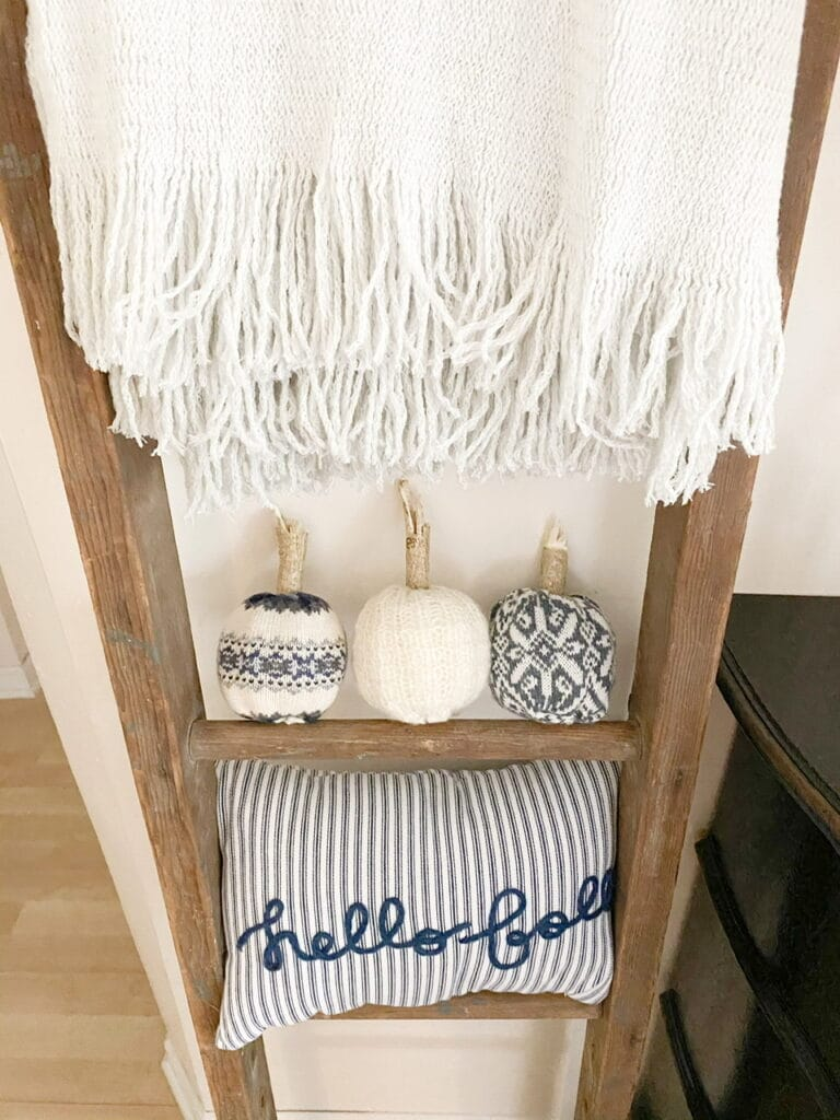 "Photo shows the 3 completed DIY sweater pumpkins sitting on an antique ladder underneath a grey throw blanket and above a blue and white striped pillow that says ""hello fall"""