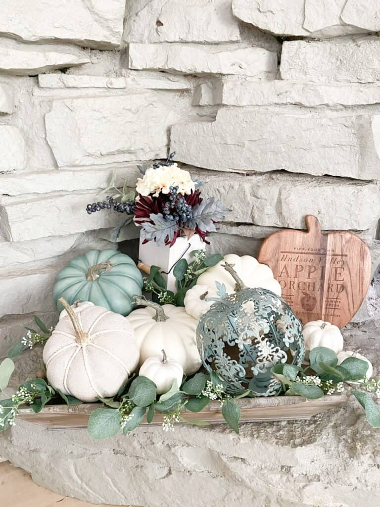 Muted fall decor, a collection of white and heirloom pumpkins mixed with eucalyptus leaves in a wooden tray. A fall bouquet of flowers with a wooden apple orchard sign.