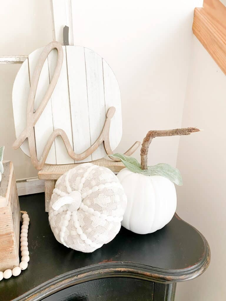 "Neutral fall decor, a white pumpkni with a stick stem, a gray and white patterned fabric pumpkin, a white wood pumpkin sign with a wood ""hi"" in front of it."