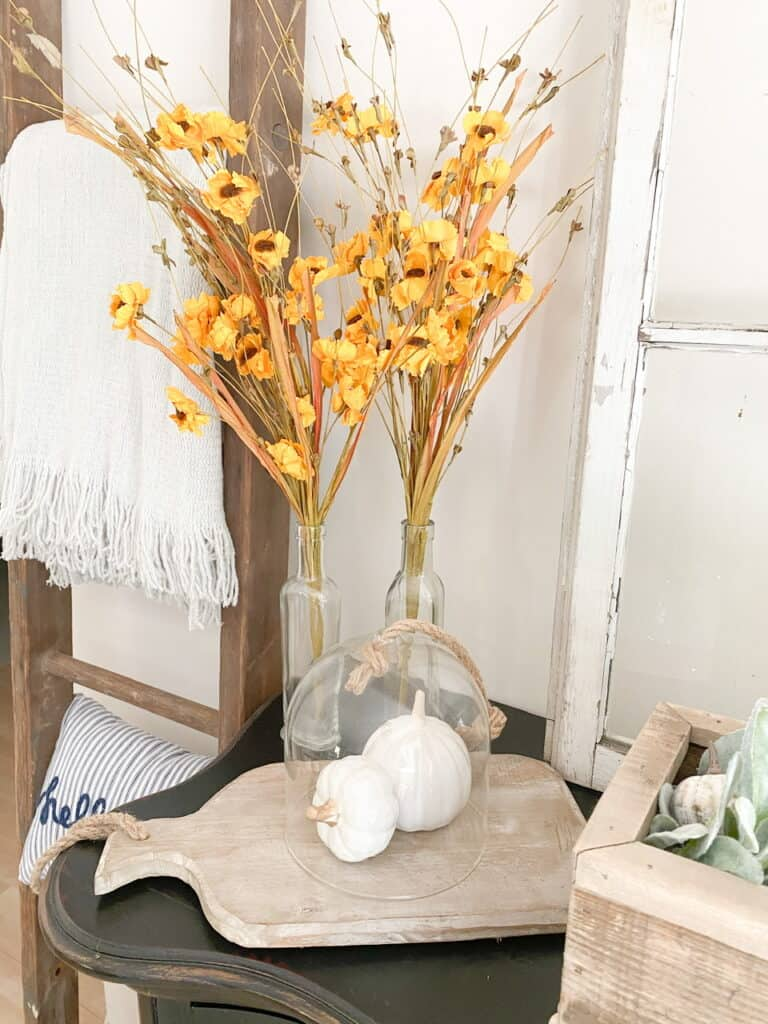 Some muted fall decor pieces, muted yellow flowers in glass bottles, a wood tray with 2 white pumpkins under a cloche.
