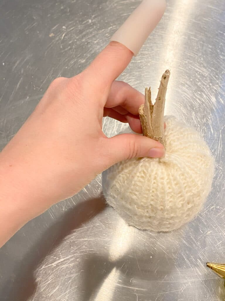 Photo shows how I used my hot glue gun to glue a stick to the top of my DIY sweater pumpkin as the stem.