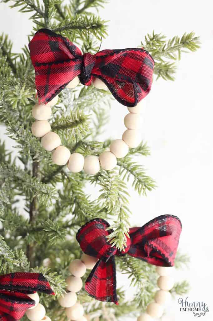 Wood bead wreath ornaments with red and black plaid ribbon hanging on a Christmas tree,