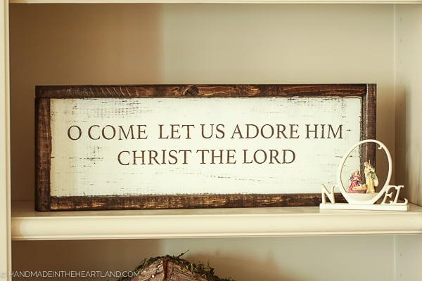 "A wood framed sign with ""O Come Let Us Adore Him, Christ The Lord"" written on it sitting on a shelf."
