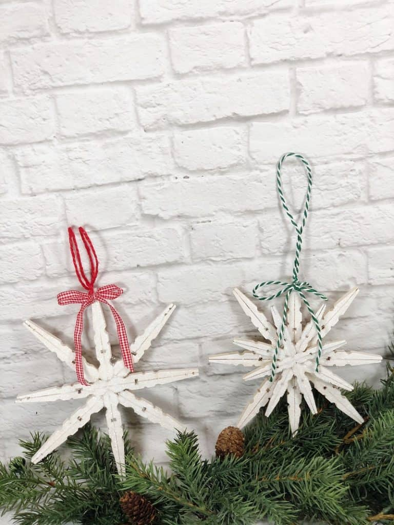 2 snowflake ornaments made out of clothespins and painted white. One has a red and white plaid ribbon and the other has a green and white striped ribbon. They are set against a white brick wall on top of a pine garland.