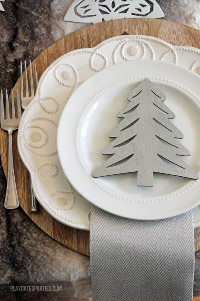 A neutral Christmas place setting. Includes a wood charger, 2 white plates with ornate detailing along the edges, 2 forks, a white and gray patterned napkin, and a gray wooden Christmas tree on the plates for decoration.
