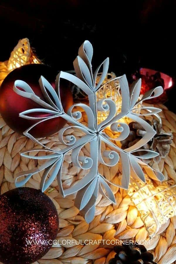 Snowflakes made from toilet paper rolls and painted white. Set on top of some red ornaments and white pinecones and lights.