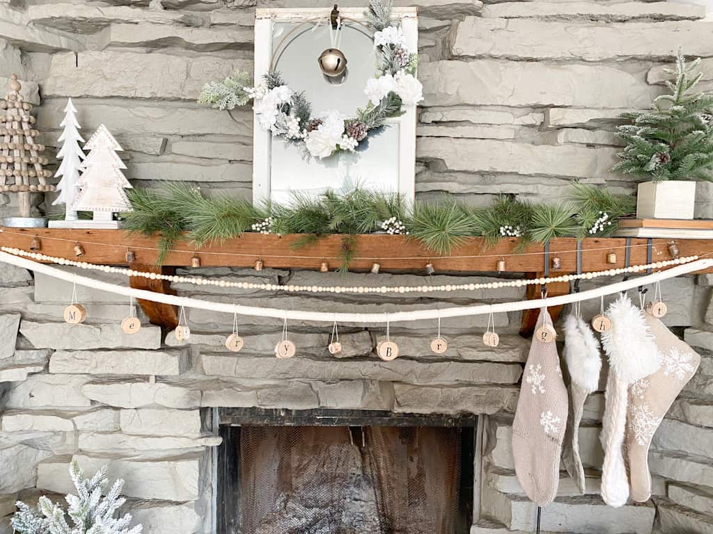 DIY Christmas Mantle Garlands. Image shws a fireplace decorated for Christmas with a garland, a mirror with a wreath, some faux pine trees, stockings, and 3 garlands. One if made from bells, one made from wood beads, and one made from pieces of wood with the words Merry & Bright on it.
