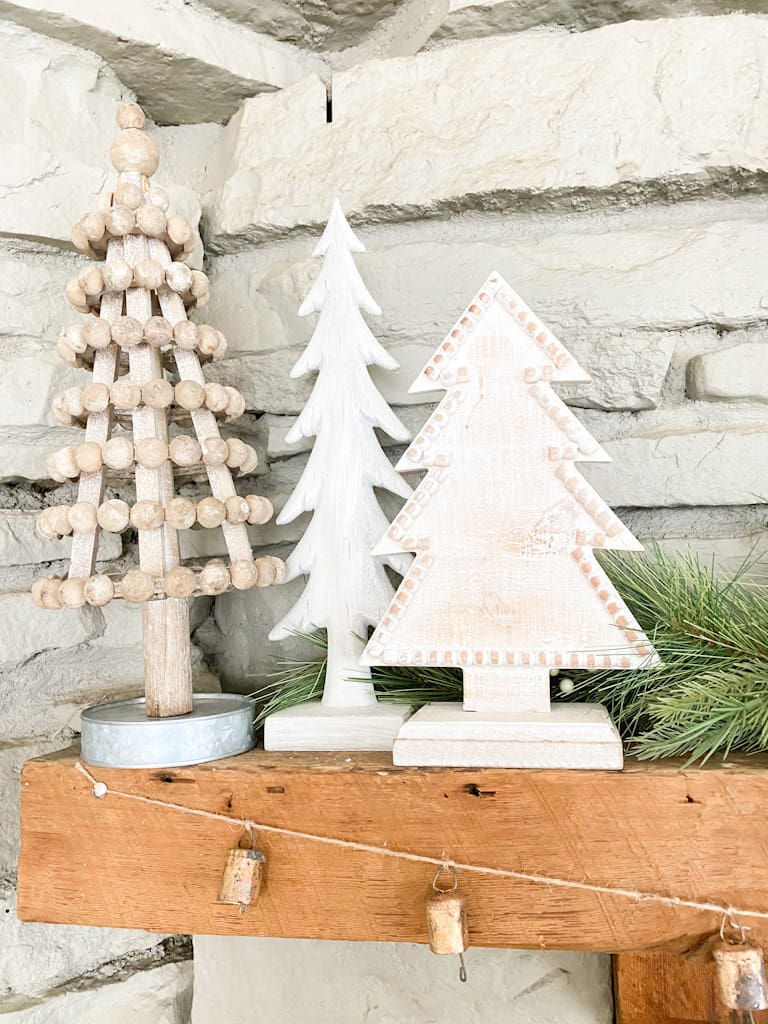 A set of 3 wood trees on a wooden mantle with some spruce branches behind them. One tree is a wood bead tree that is slightly whitewashed with a metal base. The other 2 are painted white and one is taller and skinner, the other is wider and has some wood beads outlining it.