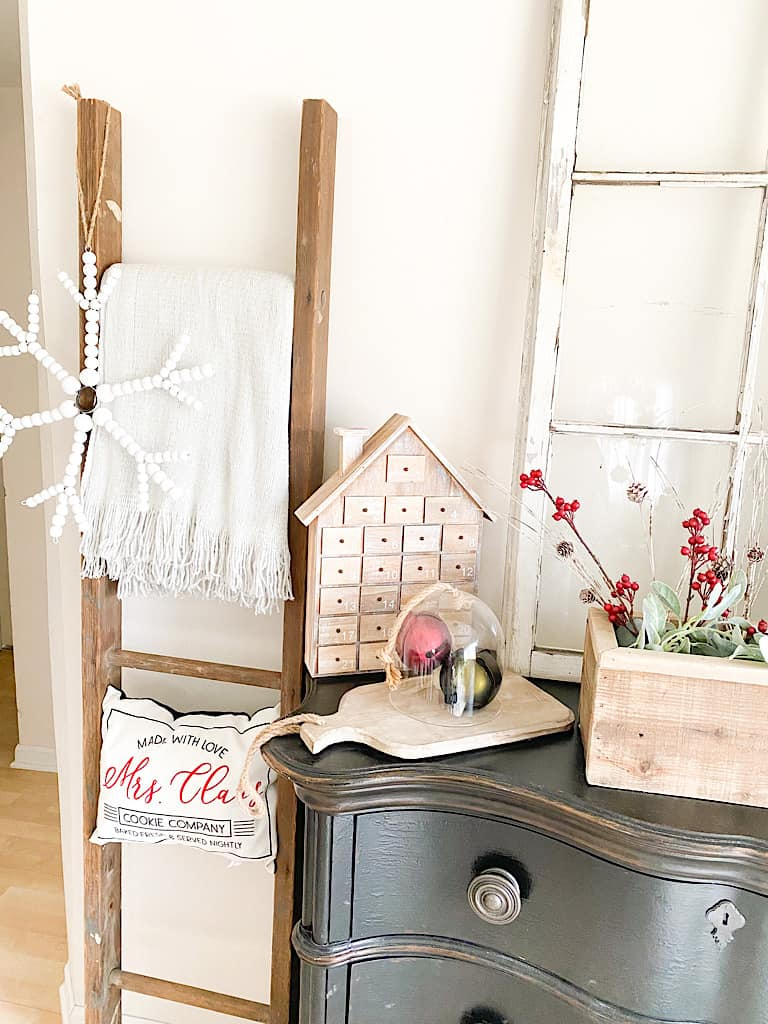 An old ladder with a gray throw blanket, a Mrs. Claus pillow, and a white wood bead snowflake hanging on it. Next to that is the edge of a black dresser with a wooden house advent calendar, a large red and a large green jingle bell under a glass cloche and on top of a wood paddle cutting board.
