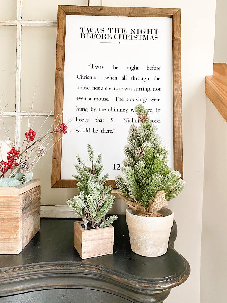 2 mini faux pine trees, one in a wood box and the other in a ceramic pot are in front of a wood framed sign with a passage from The Night Before Christmas.