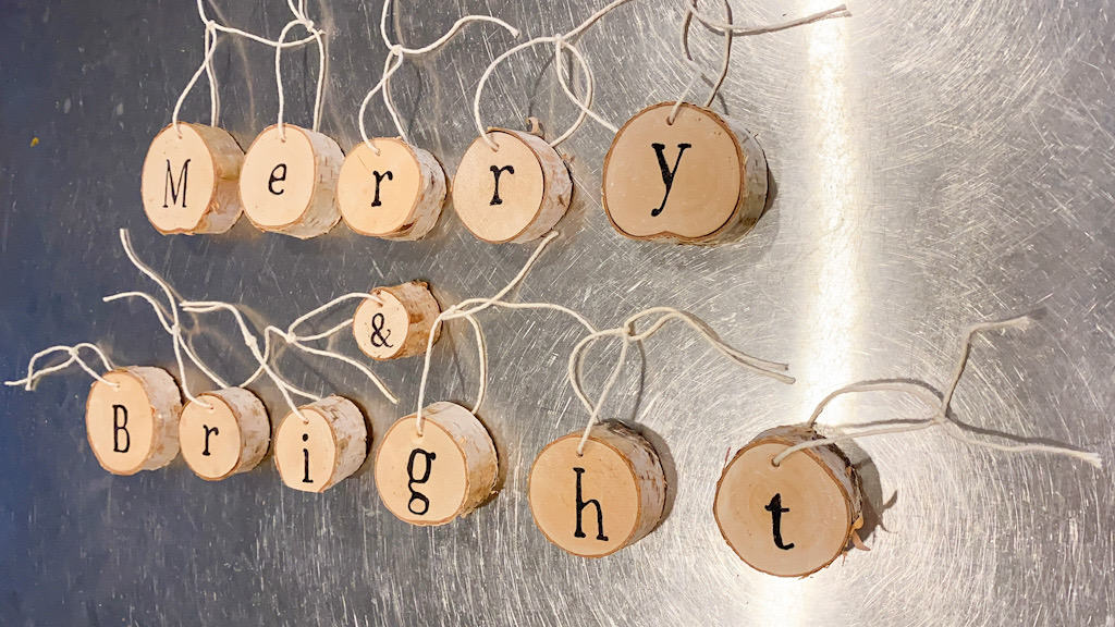wood slices with the words Merry & Bright written on them with cream string tied to them,