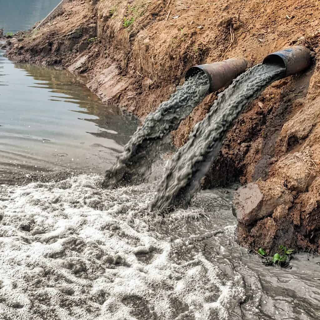 Photo shows polluted water being dumped into a natural body of water. One of the benefits of shopping second hand is that you lessen the demand for new clothing to be produced and therefore less water pollution will occur.