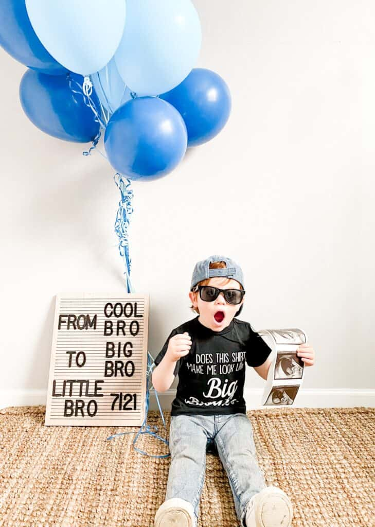 """A toddler boy wearing a baseball cap backwards, black sunglasses, and a t-shirt that says """"does this shirt make me look like a big brother?"""" He is sitting next to a letter board that says """"From cool bro to big bro. Little bro 7