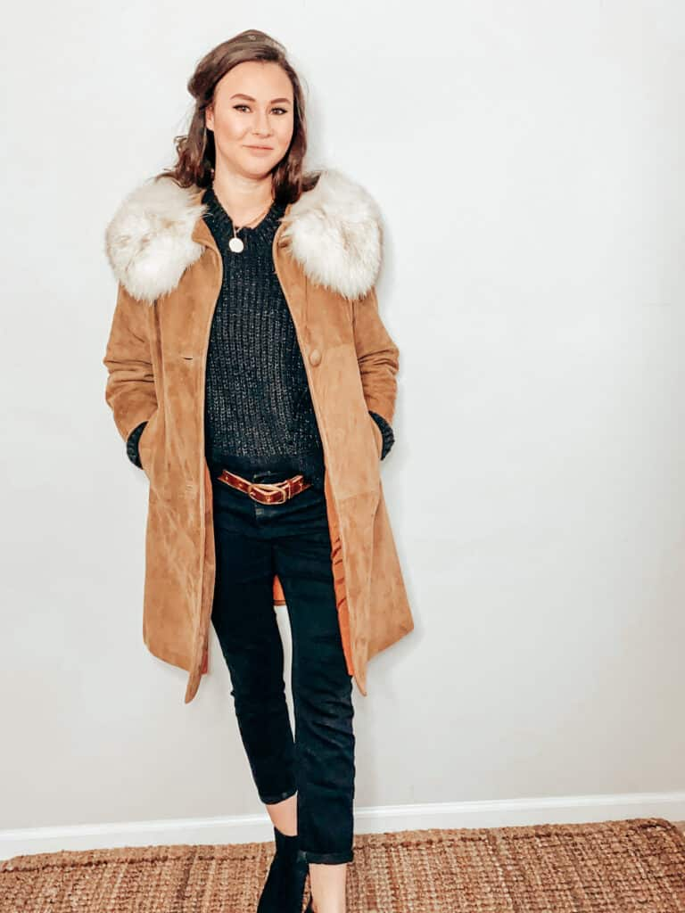This thrifted winter outfit is made up of a camel color suede and faux fur jacket over a black knit sweater, paired with some black skinny jeans, a brown belt, a gold medallion necklace, and some black faux suede boots.