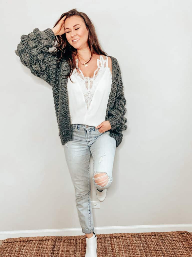 This thrifted winter outfit is a dark gray chunky knit cardigan over a white camisole with a lace panel down the front center of the top, paired with some light wash high rise jeans with some distressing and holes, a gold medallion necklace, and some white faux snakeskin ankle boots.