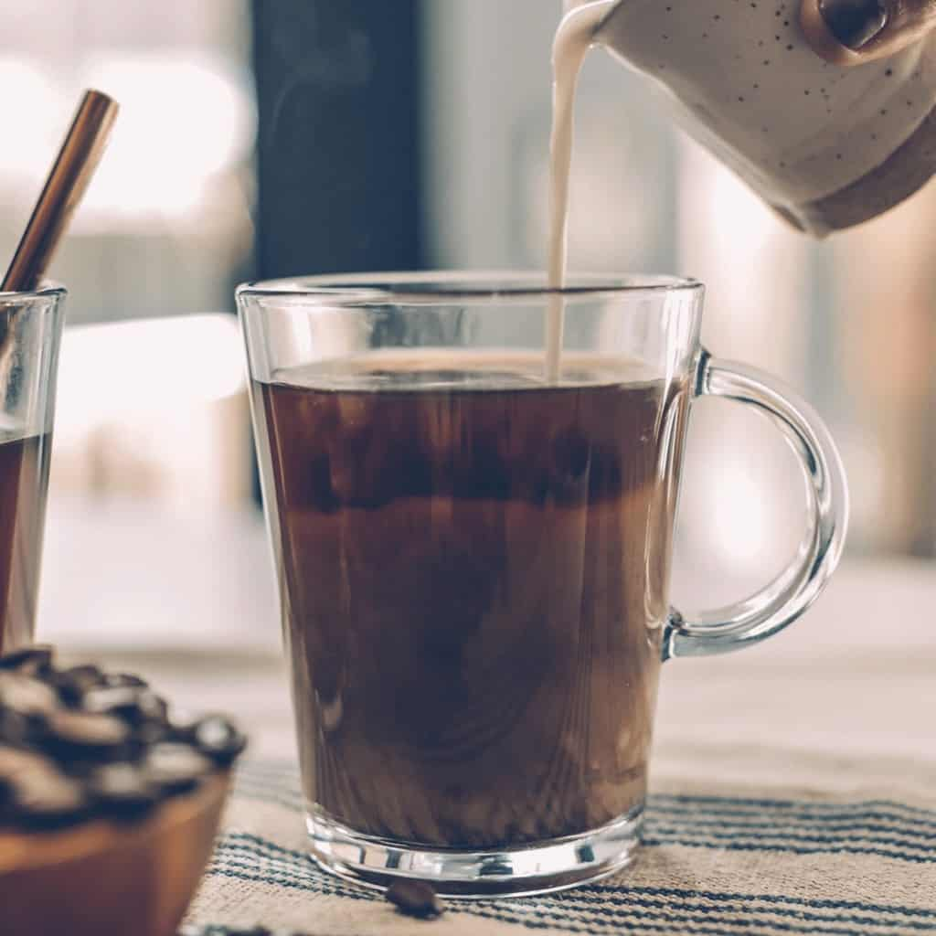 Image shows 2 clear coffee mugs filled with coffee. One mug has some creamer being poured into it. There is a bowl filled with coffee beans.