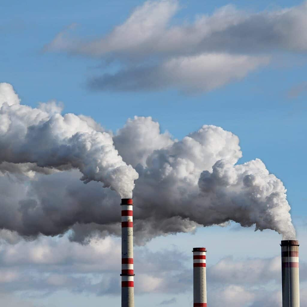 Photo shows 3 smoke stacks releasing pollution into the air. One of the benefis of shopping second hand is that you lessen he demand for new clothing and can help to reduce the amount of pollution released from its production.