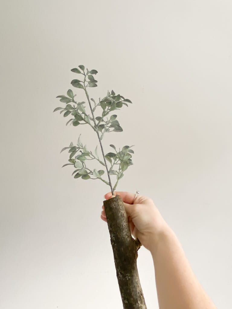 A hand holding in place one of the small faux stem branches at the top of the fake tree.
