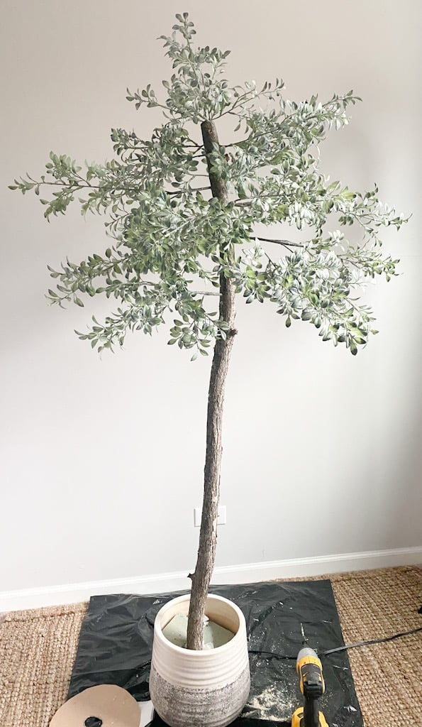 The fake tree after all the branches have been glued on, inside it's pot.