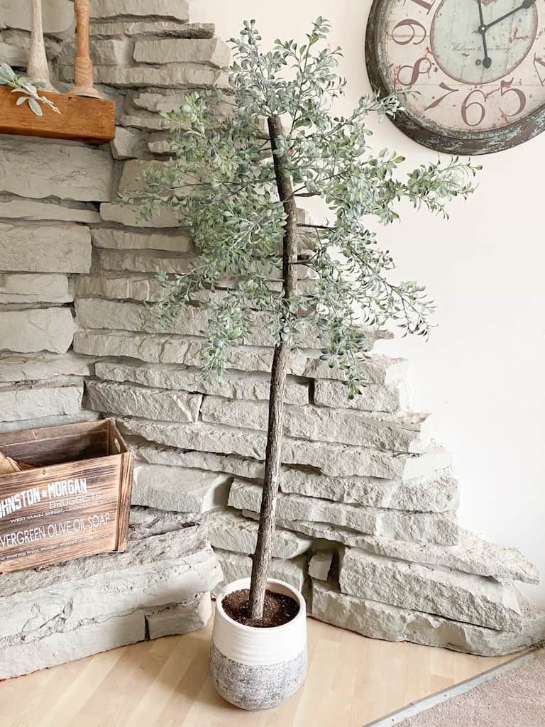 Check out how to make a fake tree for your own home that looks super realistic. Photo shows an artificial potted tree in front of a stone fireplace with a wooden box on the ledge.