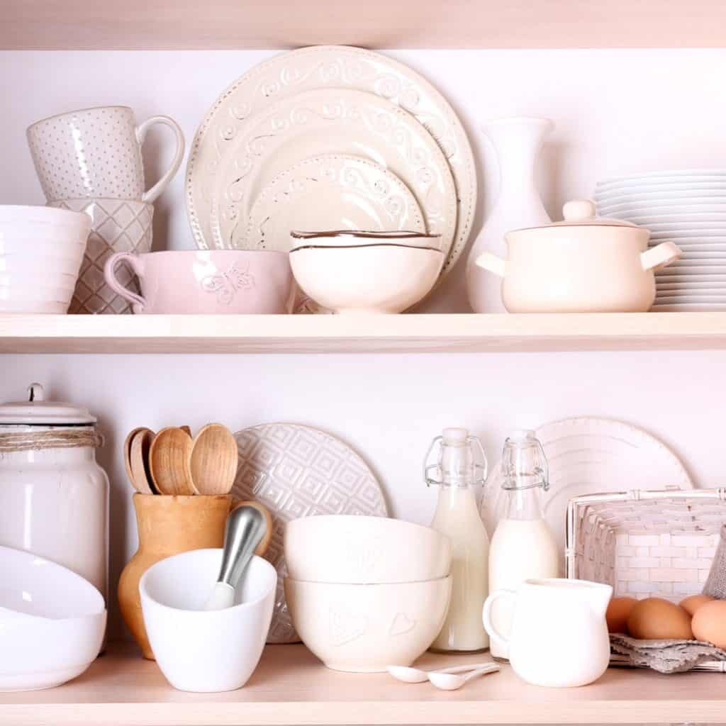 Light wood shelves with a variety of white tableware and a mixture of wood and white kitchen items. There are also some glass kitchen items mixed in.