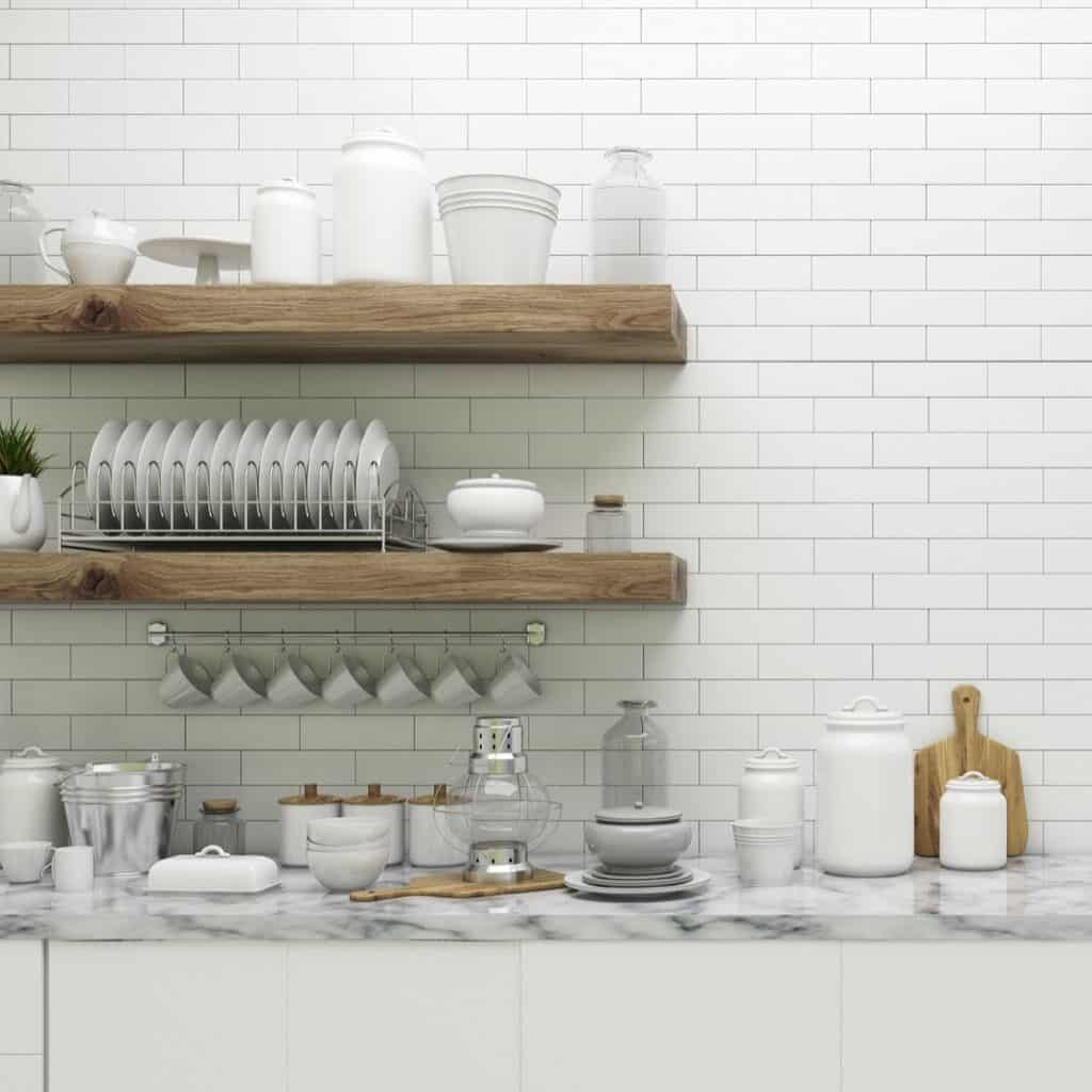 Thick wood floating shelves with various white and glass dishware and kitchen items. There are also some jars with labels and a few wood kitchen items mixed in as well.
