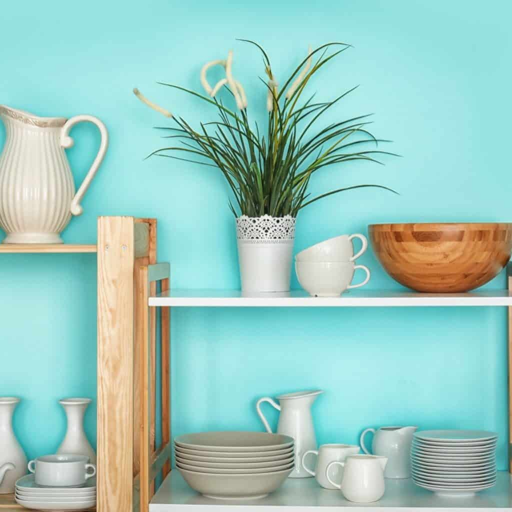 Wooden shelves with a variety of white kitchen ware mixed with wood kitchen items and a plant in a white pot.