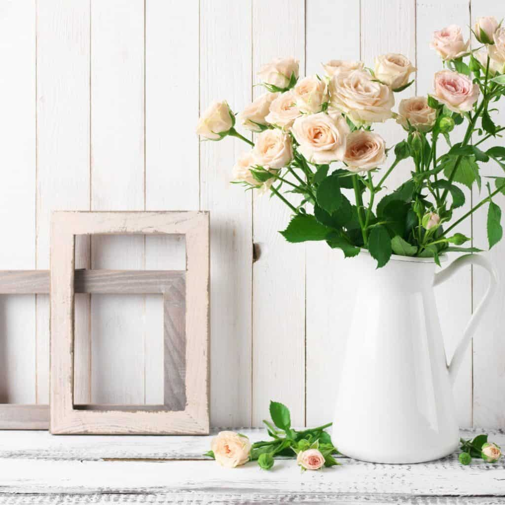 Some light pink roses in a white pitcher next to 2 empty wood frames. These are sitting in front of a white shiplap wall.