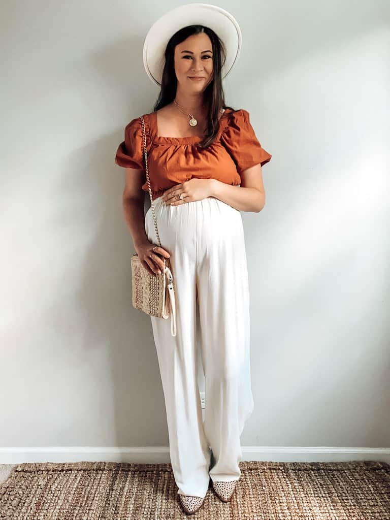 A pregnant woman wearing a rust colored cropped shirt with some high rise cream casual trousers, a wide brim hat that is cream, a straw bag with a gold chain, and some leopard print boots.