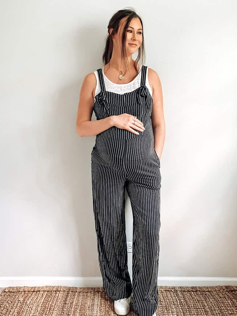 A pregnant woman wearing black and white striped overalls with a white eyelet tank underneath, some gold necklaces, and white sneakers. These are both maternity second hand clothes that are actually regular clothes you can wear while pregnant.