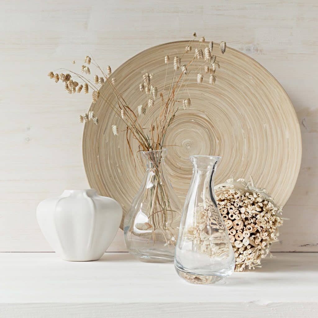 A light wood large dish sitting up against a white wall, in front of it are 2 glass vases one of which has some dried florals in it, a white ceramic vase, and a cluster of dried straw.