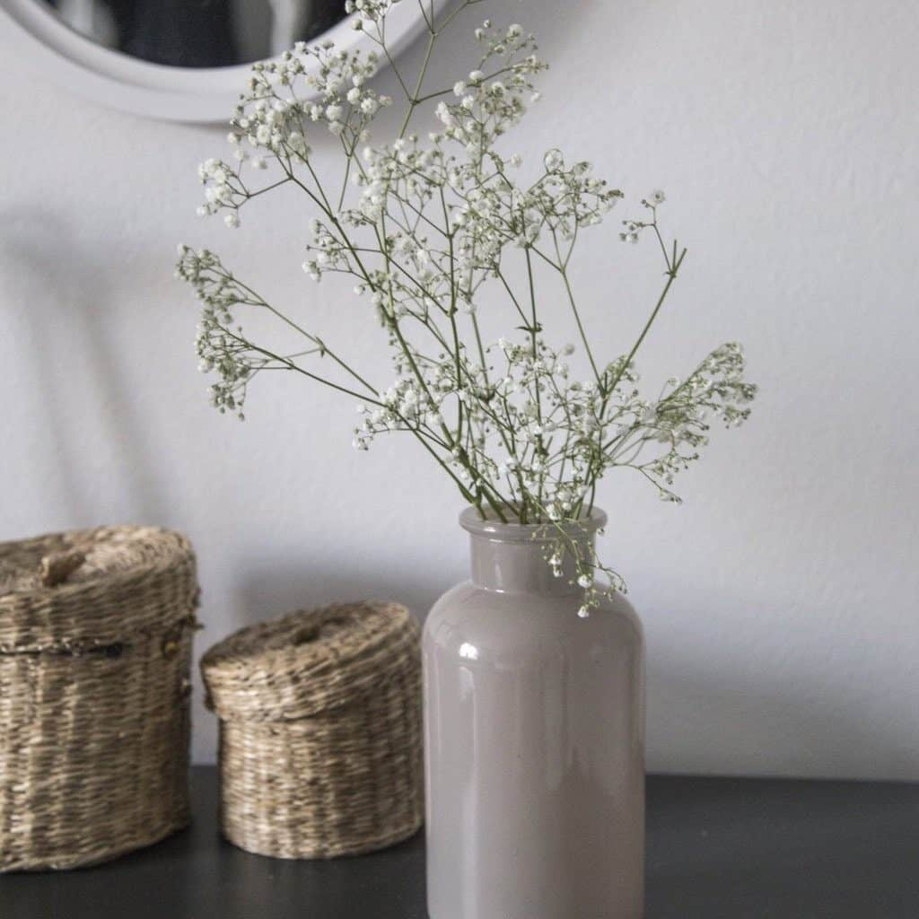 Some baby's breath in a warm tone gray vase next to 2 wicker containers with lids sits on a black table in front of a white wall and there is the edge of a white framed round mirror showing at the top of the photo.