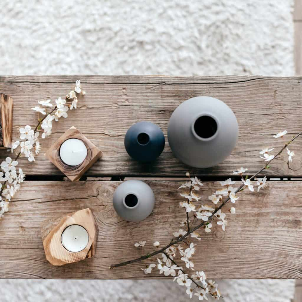 A weathered wood bench with assorted gray vases, 2 small wooden candle holders with tea lights in them, and 2 sprigs of flowers.