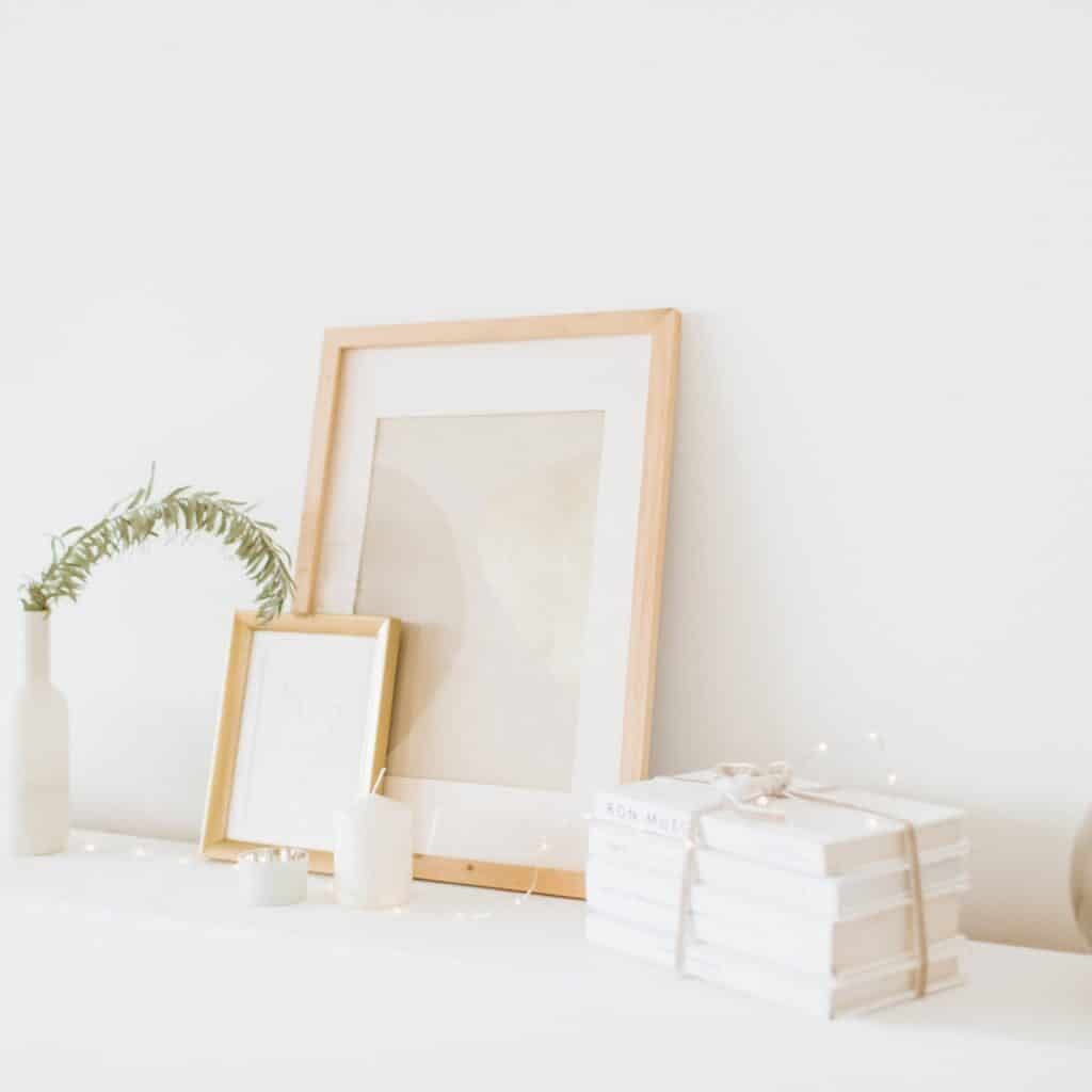 2 light wood framed pieces of art with a stack of white books bound by string, and a white vase with a little greenery sticking out of it.