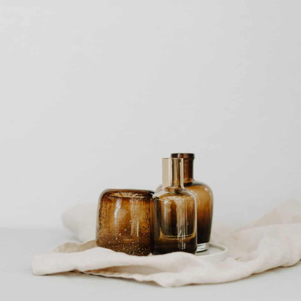 3 amber glass bottles on a cream cloth in an all white space.