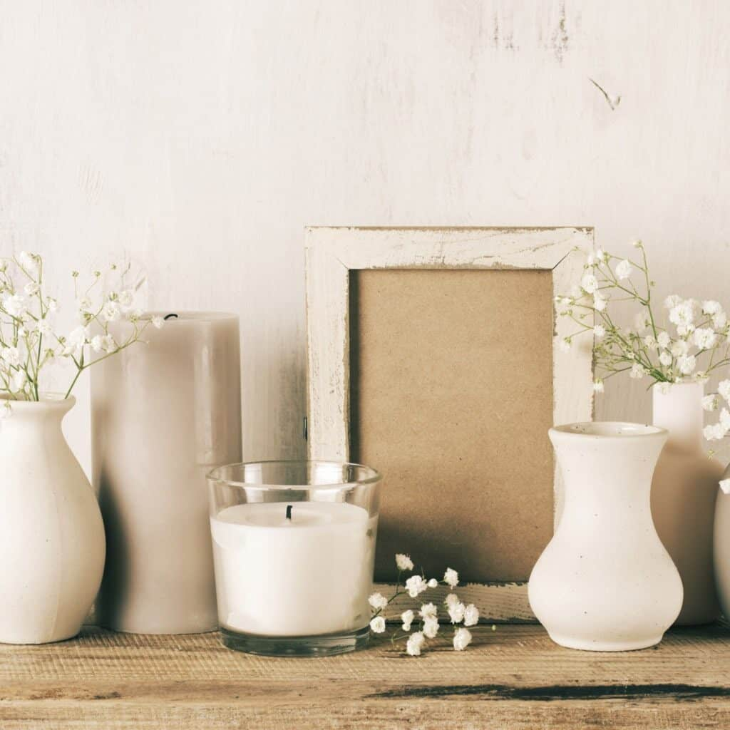 White vases with babay's breath in them, a gray candle, a white candle in a glass jar, an empty white distressed wood frame, all sitting on a weathered wood bench.