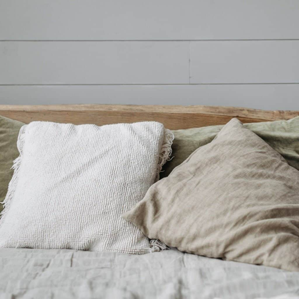 Adding neutral colored textiles will make your home oozy like this set of pillows which are white, tan, and light sage green and are a linen material. They are on top of a white linen comforter on a bed with a weathered wood headboard. The bed is in front of a white shiplap wall.