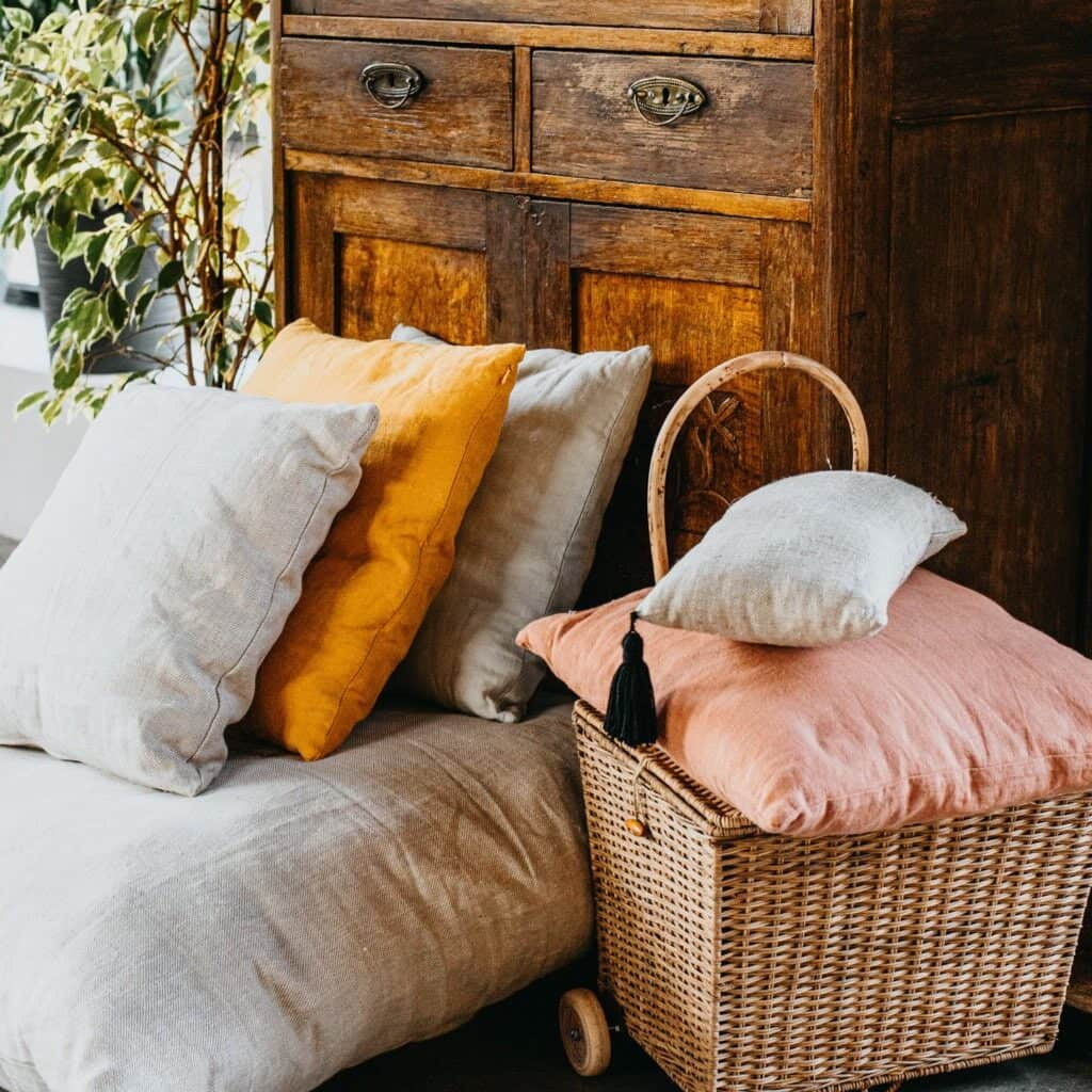 Some cream pillows mixed with a marigold and soft pink pillow which is in a wicker basket with a handle next to a couch which is in front of an antique cabinet and there is a potted houseplant next to it.