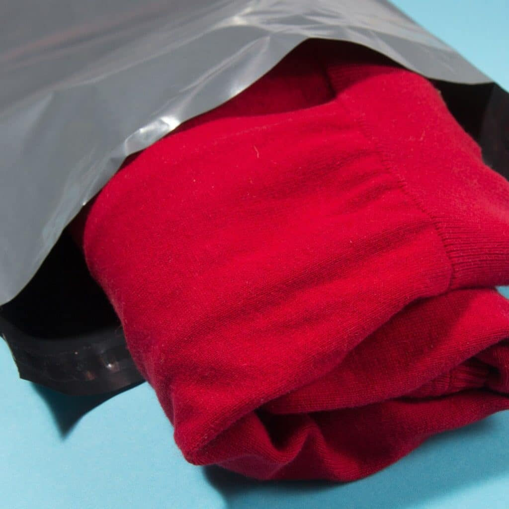 A folded red sweater being placed in a gray plastic mailer.