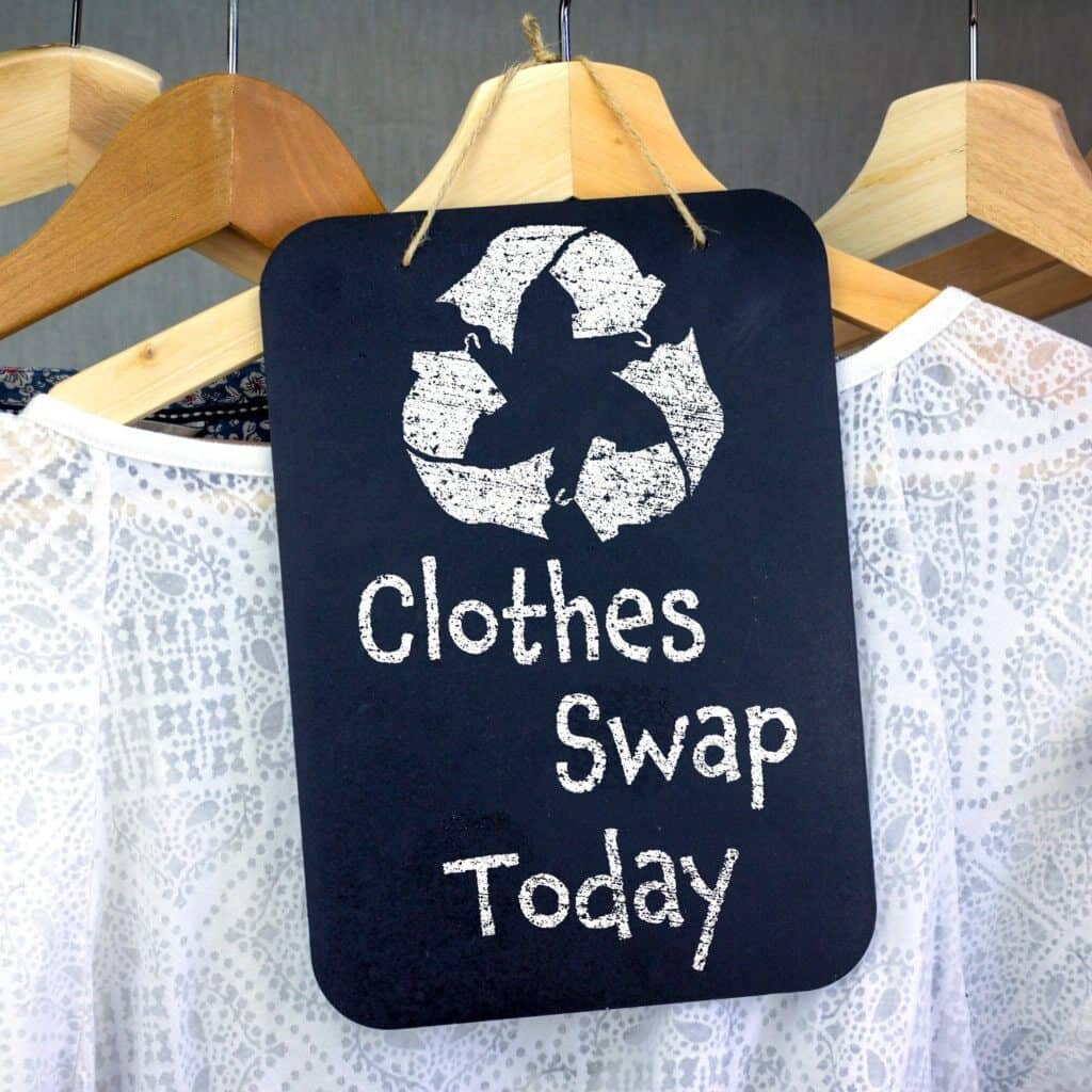 """A white shirt on a wooden hanger with a sign in front of it that says """"clothe swap today"""" with a recycle sign at the top."""