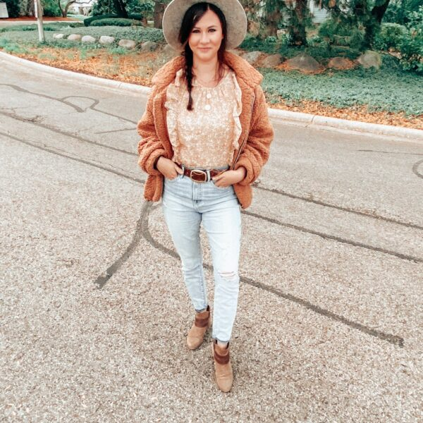 A woman standing outside wearing a gray wide brim hat, a yellow floral top under a brown teddy bear style jacket, some light wash high rise jeans with a belt, and brown ankle boots.