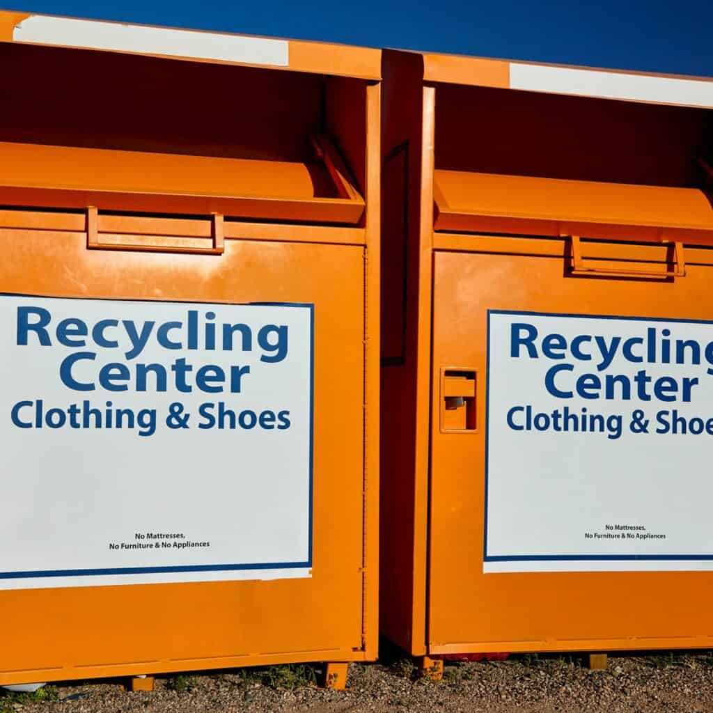 """2 orange metal bins with signs that say """"recycling center, Clothing and shoes."""" Recycling old clothes by dropping them off at clothing recycling bins."""